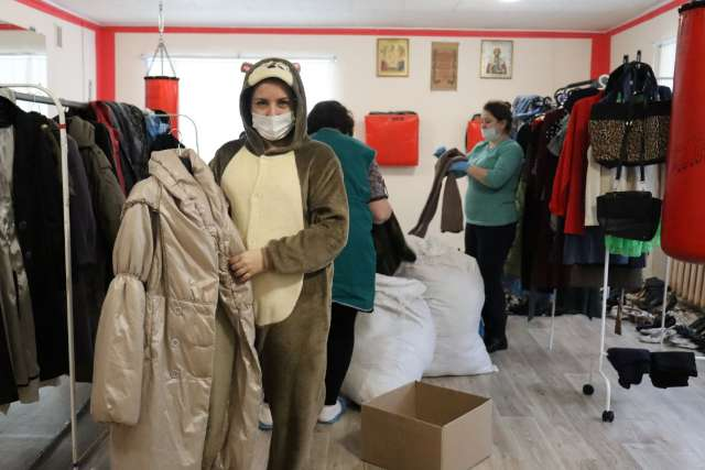 Сотрудники Демянского КЦСО помогают посетителям благотворительного магазина подобрать нужные семьям вещи.