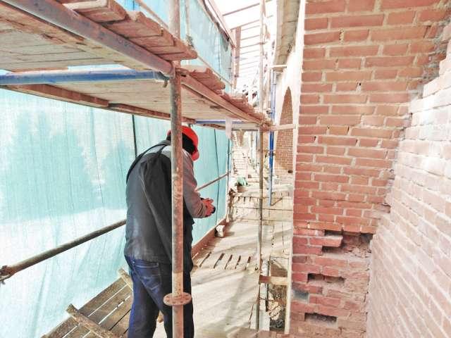 Реставраторы удаляют из крепостной стены повреждённые кирпичи. Потом на их место установят новые.