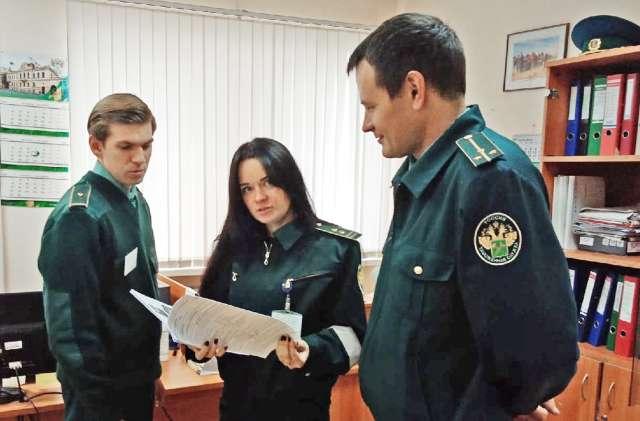 Сергей Баранов (справа) обсуждает с таможенными инспекторами план осмотра машин с грузами.