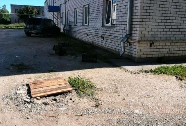 Люк на улице Заводской Домострой в Малой Вишере закрыли деревянным щитом.